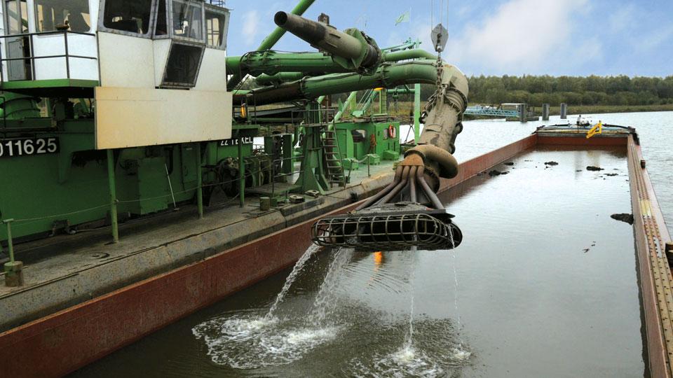 Barge unloaded by hopper dredger.